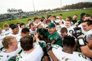 Mike Holmes, center, is surrounded by his players after their victory over Mendon during this past season's playoffs. Photo/Tim Reilly