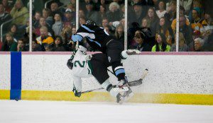 Mona Shores' Jared Karnitz delivers a big hit to Reeths-Puffer's Derreck Pleiming along the boards during Sunday's game at Lakeshore Ice Centre. Photo/Tim Reilly