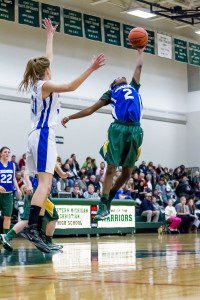 Momo Neal reaches for the ball past the outstretched arms of WMC's Rachel Bruinsma. Photo/Tim Reilly
