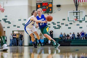 Muskegon Catholic's Katherine Salisz dribbles the ball while being defended by WMC's Sarah Hughes. Photo/Tim Reilly