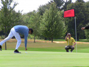 Travis Clarke (right) lines up his put on 14 as Ryan Mouw prepares to approach his putt.