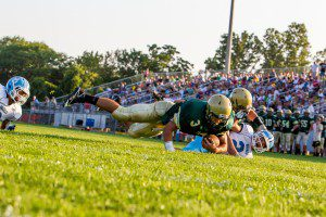 Nick Holt dives across the end zone for Muskegon Catholic.