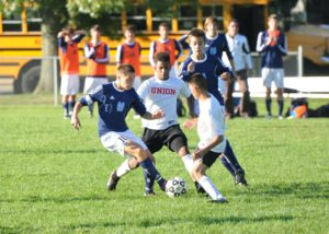 Mona Shores senior Christian Zirchauer breaks between two Union players Wednesday. (Photo by Eic Sturr)
