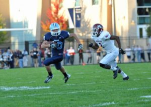 Mona Shores sophomore Hunter Broersma is chased down by Muskegon senior John Hall. (Photo by Eric Sturr)