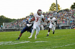 Muskegon senior Deshaun Thrower is wrapped up by Mona Shores senior Michael Grissom Friday night. (Photo by Eric Sturr)