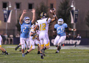 Grand Haven senior Karl Johnson looks to pass over Mona Shores' Jacob Workman. Photo/Eric Sturr