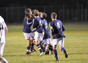 Mona Shores players celebrate freshman Kevin Quiqq's game-winner on a penalty kick in the second overtime period. (Photo by Eric Sturr)