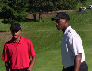 Devon Kitchen and Byron Scott discuss a shot during the first Annual Flex Alexander Celebrity Golf Outing at the Muskegon Country Club.