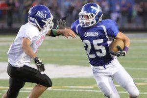 Oakridge running back Dan Shoop provides a stiff arm to a Ravenna defender Friday night. (Photo by Jeff Peterson)
