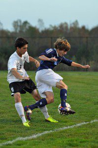 Mona Shores junior Nate Hoover takes the ball down the pitch past Zeeland East's Edward Elderkin. (Photo by Eric Sturr)