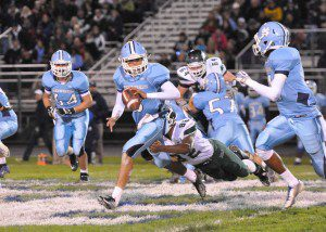 Mona Shores junior Tyree Jackson pitches at the last second as he is being tackled by Reeths-Puffer's Evan McCrary. Photo/Eric Sturr