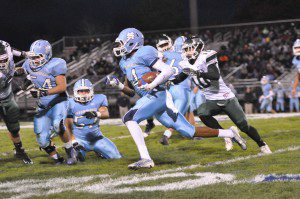 Mona Shores senior Marquon Sargent takes the ball outside chased by the Rockets' Austin Malotke. Photo/Eric Sturr