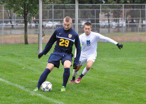 Grand Haven's Mike Moran shields the ball from Mona Shores' Christian Zurchauer. Photo/Eric Sturr