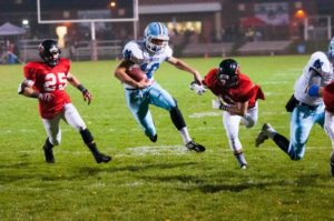 Shores' Hunter Broersma escapes from Lowell's Jacob Stepens for a few more yards Friday night. Photo/Eric Sturr