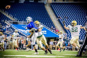 Catholic's Jacob Holt drills Beal City QB Kurt Gross, a frequent occurrence at Friday morning's Div. 8 title game. Photo/Tim Reily