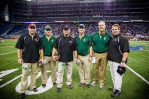 Six lives connected by Muskegon-area football, from left, Muskegon assistant coach Justin Ego, Catholic assistant coach Scott Fodrocy, Muskegon head coach Shane Fairfield, Muskegon Catholic head coach Steve Czerwon, Catholic assistant coach Mike Ribecky, and Muskegon assistant coach Brent White. Photo/Tim Reilly