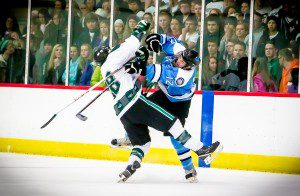 Mona Shores' Ben Essenberg delivers a hit to Reeths-Puffer's  Tommy Roswell during first-period action. Photo/Tim Reilly