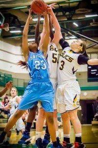Jana'a Matthews pulls down the rebound against Grand Haven No. Lynn Olthof and Taylor Craymer. Photo/Tim Reilly