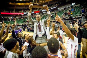 Muskegon head coach Keith Guy hoists the Class A state title trophy after his Big Reds defeated Bloomfield Hills 91-67. Photo/Tim Reily