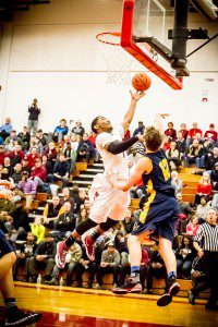 Deshawn Thrower drives to the basket against Grand Haven's No. 12 Noah Lein. Photo/Tim Reilly