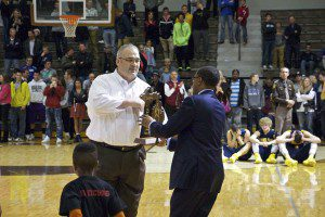 Muskegon coach Keith Guy accepts the Class A regional championship trophy in hist teams' 56-48 win over Hudsonville. Photo/Jason Goorman