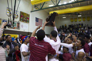 Deshaun Thrower celebrates with teammates and students with the trophy. Photo/Jason Goorman