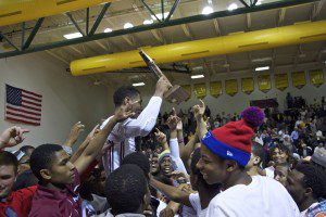 Muskegon students hoist Deshawn Thrower on their shoulders after the senior guard's 28 point performance. Photo/Jason Goorman