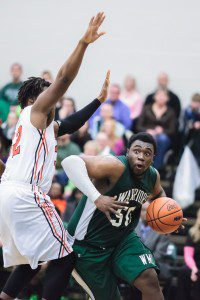 WMC's Bernard Smith drives baseline against No. 32 Marquis Gresham. Photo/Randy Ricksen