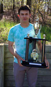 Tyler Trovinger stands with the Home Run Derby trophy coach Lent rehabbed from the trophy case for the event.