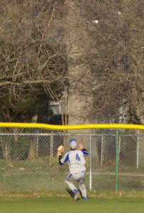Wyatt Hilton reaches the fence chasing a Jacob Holt home run. Photo/Jason Goorman