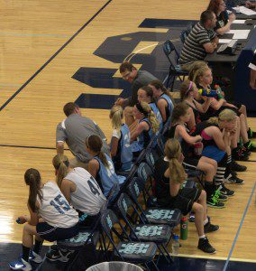 Two different girls teams sit on their benches at Mona Shores field house on Saturday.
