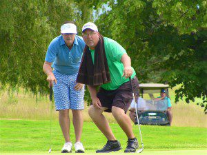 Ryan Mouw and Reeths-Puffer golf coach Chris Carter line up a put. Mouw beat Carter in the semifinals on a 19-hole play off.