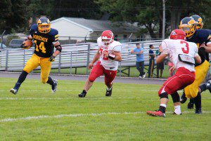 North Muskegon's Logan Waller rushes past Holton defense. Photo/Jason Goorman