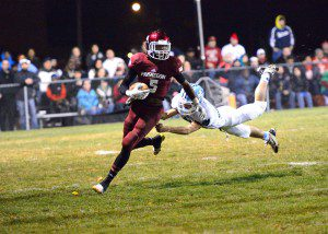 Muskegon senior Joeviair Kennedy (5) escapes a Shores tackler to the outside. Photo/Tim Reilly