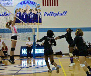 Muskegon's Lanesha Spencer makes the hit as Mona Shores' Madison Dunn prepares for the block. Photo/Jason Goorman
