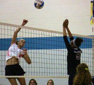 Keziah Brown spikes the ball past Muskegon's No. 9 Savanna Roberts. Photo/Jason Goorman