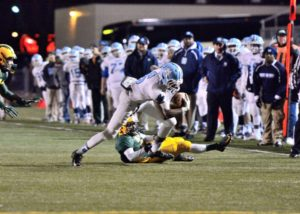 Kobe Burse breaks a tackle on a reception to the outside for Mona Shores. Photo/Eric Sturr