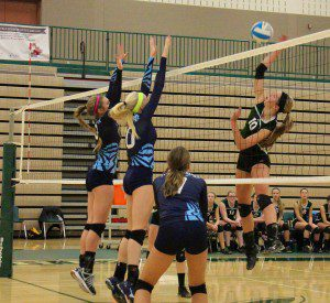 Reeths-Puffer's Kate Uganski spikes the ball as Mona Shores' Raelyn Sells (right) and Courtney Brewer try to block. Photo/Jason Goorman