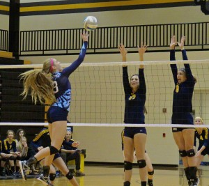Grand Haven's Sophia Newhouse and ? try to block Mona Shores spiker Courtney Brewer. Photo/Jason Goorman