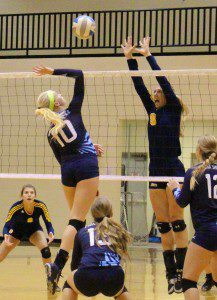 Mona ShoresRaelyn Sells goes for the spike as Grand Haven's Autumn Monsma goes for the block. Photo/Jason Goorman