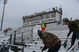 Darece Roberson Sr. and Roger DeYoung shovel snow off the Mona Shores football stadium bleachers. Photo/Jason Goorman