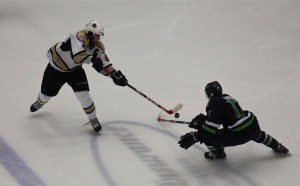 Christian Wolanin goes for the lose puck against Bloomington's Tarek Baker. Photo/Jason Goorman
