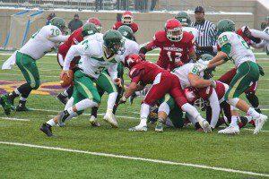 Zeeland West quarterback Casey Brinks looks to deceive the Muskegon defense on the run. Photo/Jason Goorman