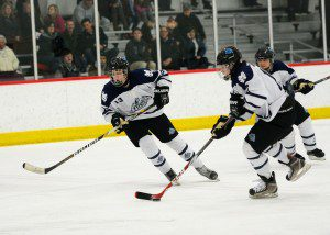 Mona Shores' Carter O'Neil (10) moves the puck through the neutral zone with Sawyer Jenson (13). Photo/Eric Sturr