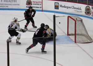 Muskegon's Michael Latorella posts a key save in the last minute of play. Photo/Jason Goorman
