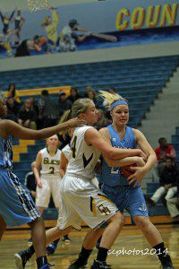 Grand Haven's Lauren Strong tries to fight the ball away from Jenna Matthews. Photo/Carol Cooper
