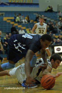 No. 24 Kobe Burse looks to pick up the loose ball from Grand Haven's Ross Koella. Photo/Carol Cooper
