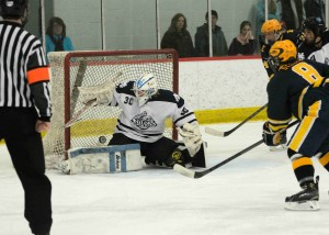 Mona Shores' Jake VanderLee (30) swipes away a save on his way to shutting out East Grand Rapids.  Photo/Eric Sturr