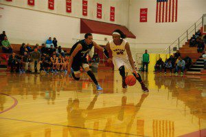 Joeviair Kennedy drives around Grand Rapids Christian's No. 14 Deleon Brown. Photo/Tim Driscoll