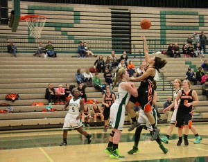 Kali Wahr floats a shot in the lane as Reeths-Puffer's Brooke Larabee attempts to take the charge. Photo/Jason Goorman